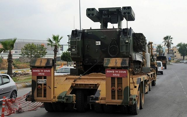 A Turkish military truck transports a mobile missile launcher to the Syrian border, in Iskenderun, Turkey, on Wednesday.  (photo credit: AP Photo)