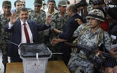 Muslim Brotherhood presidential candidate Mohammed Morsi waves after casting his vote at a polling station in Zagazig, Egypt on Saturday. (photo credit: Amr Nabil/AP)