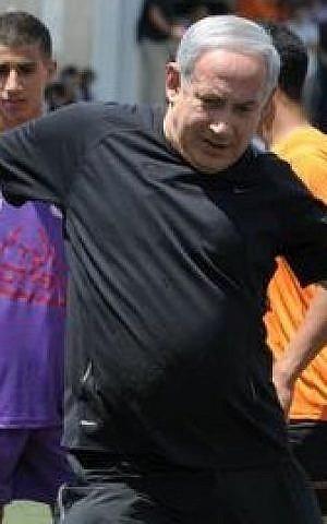 Prime Minister Benjamin Netanyahu kicks a soccer ball at Kraft Stadium in Jerusalem on Monday. (photo credit: Moshe Milner/GPO)