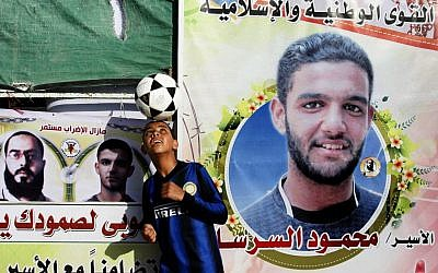 A Palestinian boy plays with a football in front of banners forming part of a protest tent in solidarity with Palestinian prisoner Mahmoud Sarsak last week. (photo credit: Abed Rahim Khatib/Flash 90)