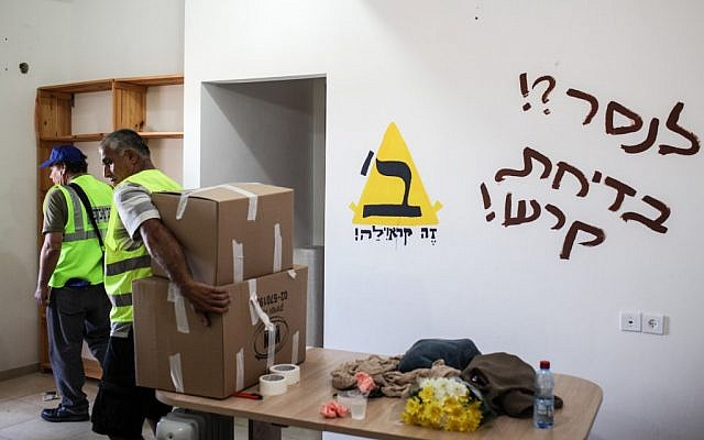 "Defense Ministry workers moving belongings out of an Ulpana home Tuesday. The graffiti read: ""To saw? A stupid joke!"" a reference to a nixed plan to move the actual homes to another site. (photo credit: Noam Moskowitz/Flash90)"