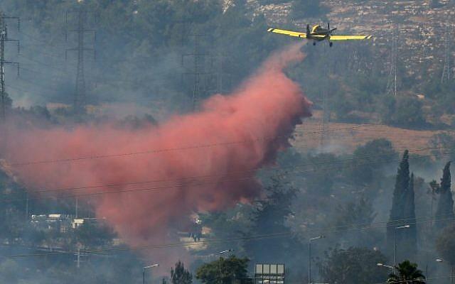 Illustrative: A firefighting plane sprays flame retardant on a forest fire near Motza, on the outskirts of Jerusalem. (Nati Shohat/Flash90)