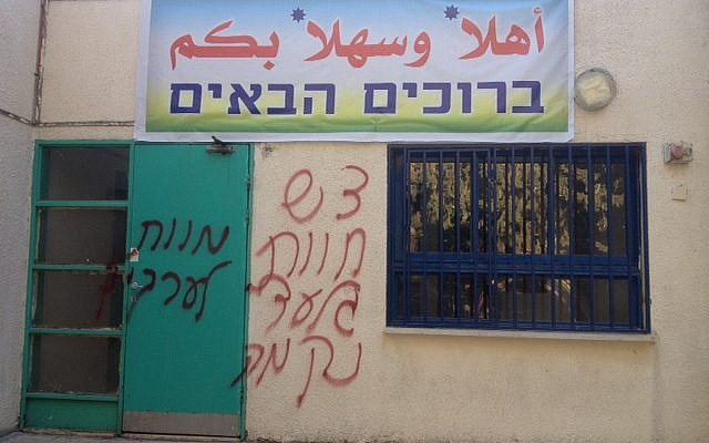 Graffiti reading 'Death to Arabs' and 'Regards Havat Gilad' and 'Revenge' on the door of a Neve Shalom school. (photo courtesy of Neve Shalom)