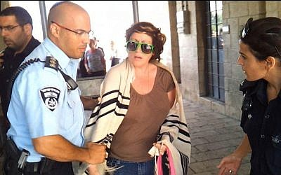 The woman being detained at the Western Wall Thursday. (photo credit: Courtesy Women of the Wall via Facebook)