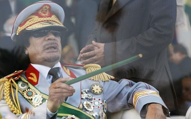 Former Libyan leader Moammar Gaddafi gestures with a green cane as he takes his seat behind bulletproof glass for a military parade in Green Square, Tripoli, Libya in 2009 (photo credit: AP/Ben Curtis)