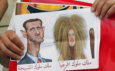 A protester holds a cartoon depicting Syrian President Bashar Assad, left, and Libya President Moammar Gaddafi, during a gathering in Paris, in April 2011, to support Syria protests (photo credit: AP/Francois Mori)