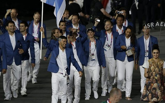 Windsurfer and Olympic medalist Shahar Zubari carries the Israeli flag as Israel's Olympic team enters the stadium during the Opening Ceremony of the 2012 London Games on Friday. (photo credit: AP/Mark Humphrey)
