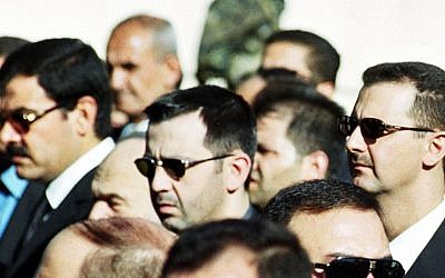 Syrian President Bashar Assad, right, his brother Maher, center, and brother-in-law Major General Assef Shawkat, left, stand during the funeral of late president Hafez Assad in Damascus, Syria on June 13, 2000 (photo credit: AP)