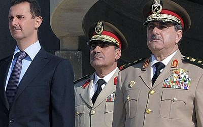 Syrian President Bashar Assad and his defense minister Dawoud Rajha (right) at a memorial ceremony for the 1973 War, October 2011 (photo credit: AP Photo/Sana)