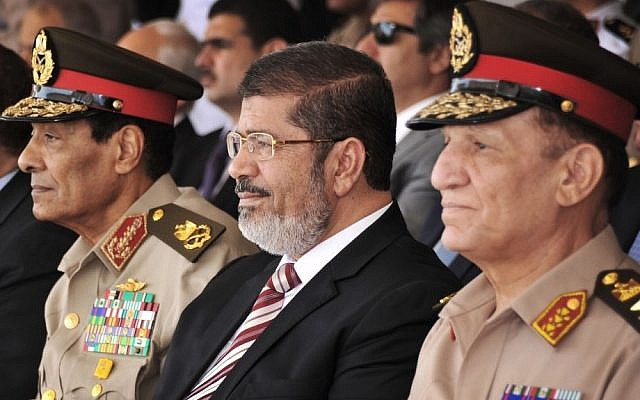 Egyptian Field Marshal Gen. Hussein Tantawi (left) and Egyptian President Mohammed Morsi (center) attend a medal ceremony at a military base east of Cairo (photo credit: Mohammed Abd El Moaty, Egyptian Presidency/AP)