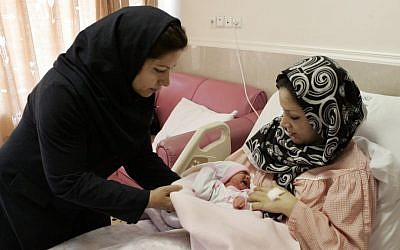 Iranian nurse Zahra Akbarzadeh, left, gives a one-day-old baby girl Setayesh to her mother, Tayyebeh Sadat Bidak, to feed her at the Mehr hospital, in Tehran, on Sunday. (photo credit: Vahid Salemi/AP)