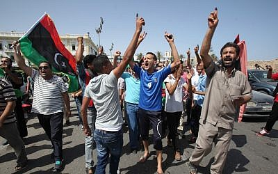 Libyans celebrate in Martyrs' Square in Tripoli after voting in the first democratic election in decades in July (photo credit: AP/Abdel Magid Al Fergany)