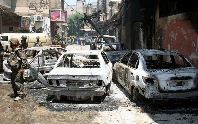 In this photo taken during a government-organized tour, Syrian soldiers stand next to burned cars after they regained control of the district of Midan, in the southern part of Damascus, Syria, Friday, July 20. (photo credit: AP)