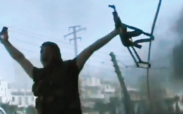 In this image made from amateur video released by the Ugarit News and accessed Monday, July 23, 2012, a Free Syrian Army soldier reacts during clashes with Syrian government troops in Aleppo, Syria. The Syrian regime acknowledged for the first time Monday that it possessed stockpiles of chemical and biological weapons and said it will only use them in case of a foreign attack and never internally against its own citizens. (photo credit: AP/Ugarit News via AP video)