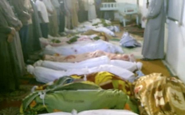 This image, taken from an amateur video, shows the bodies of dozens of victims killed in Tremseh, Syria (some nine miles from Hama) on Thursday. Rebels said the government rained shells on farmers in what they called one of the worst days of bloodshed since the uprising against President Bashar Assad's regime began. (photo credit: Hama Revolution 2011 via AP video)
