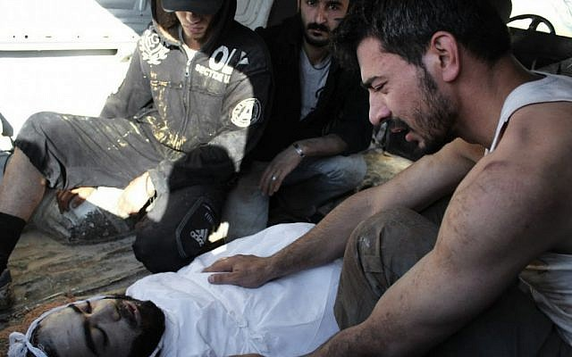 A Syrian man mourns his friend, killed Saturday in Homs (photo credit: AP Photo/Shaam News Network)