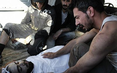 A Syrian man mourns over the body of a man killed during the fighting in Syria on Friday, July 14 (Photo credit: AP Photo/Shaam News Network, SNN)