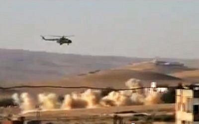 A helicopter gunship flies a bombing run in al-Qalmoun, Syria, on Tuesday, July 24, 2012. (photo credit: Shaam News Network, SNN/AP)