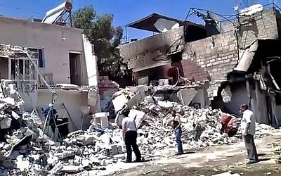 This citizen journalism image purports to show damage from heavy shelling of a district in Damascus, Syria on July 23. Iraqi refugees who sought refuge in Syria are now fleeing the violence and heading back to Iraq (photo credit: AP/Shaam News Network)