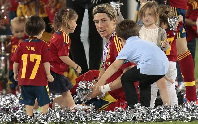 Children brought onto the pitch surround Spain's Fernando Torres after his team's 4-0 victory at the Euro 2012 soccer final on Sunday. (photo credit: AP/Ivan Sekretarev)