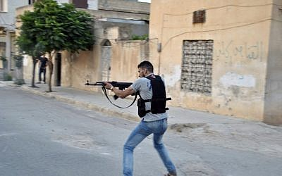 A Syrian rebel fires his weapon at Syrian troops in Idlib, Syria, July 22 (AP Photo/Fadi Zaidan)