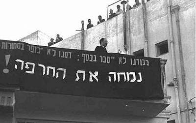 "Menachem Begin protesting against the Agreement in March 1952. The sign reads: ""Our honor shall not be sold for money; Our blood shall not be atoned by goods. We Shall wipe out the disgrace!""."
