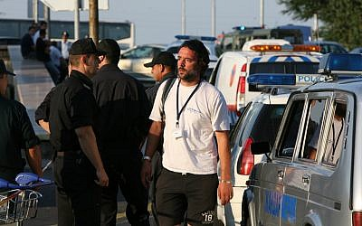 A tourist agency employee reacts as he passes by Bulgarian policemen shortly after a bomb attack against Israeli tourists near Burgas airport, on Wednesday, July 18, 2012 (photo credit: AP/Impact press Group)