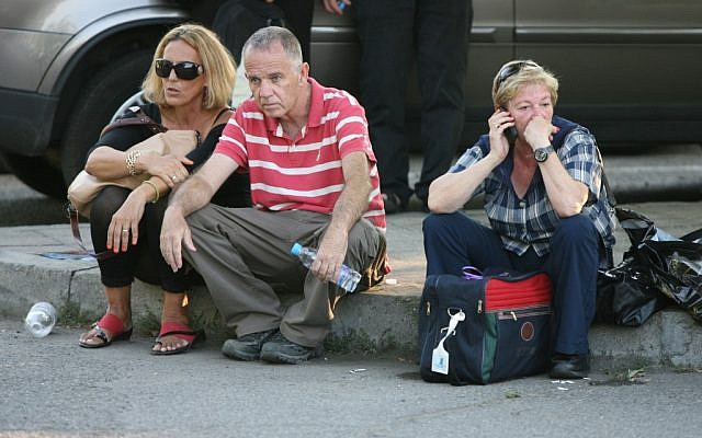 Passengers sit beside the road shortly after an explosion near Bourgas airport, Bulgaria, on Wednesday, July 18, 2012 (photo credit: AP/Impact press Group)