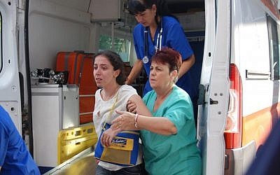 An Israeli tourist is helped as she arrives to Burgas hospital after a bus carrying Israeli tourists in the Bulgarian resort city of Burgas was blown up Wednesday, July 18, 2012 (photo credit: AP/Bulphoto Agency)