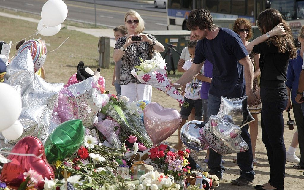 Actor Christian Bale, second right, and his wife Sibi Blazic, right, place flowers on a memorial to the victims of the mass shooting,in Aurora, Colorado. (photo credit: AP Photo/Ted S. Warren)