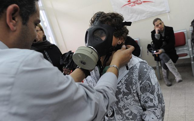 An Israeli child is trying a gas mask, part of a chemical protection kit in a distribution center in 2010. Amid growing fears that terrorist groups may inherit Syria's unconventional weapons Israelis are flocking to distribution centers to receive new gas masks. (photo credit: Gili Yaari/Flash 90)