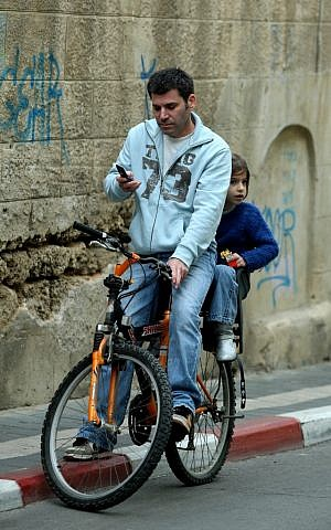 Riding without helmets and while texting (photo credit: Moshe Shai/Flash 90)