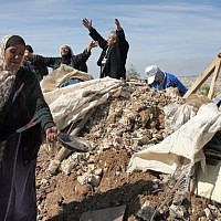 Illustrative: Palestinians try to retrieve items from the rubble of a house after it was destroyed by IDF tractors near the West Bank village of Sussiya in 2011. (Najeh Hashlamoun/ Flash90)