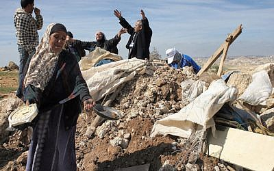 Illustrative: Palestinians try to retrieve items from the rubble of a house after it was destroyed by IDF tractors near the West Bank village of Susya in 2011. (Najeh Hashlamoun/Flash90)