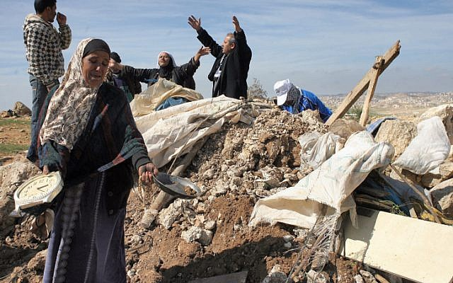 Illustrative: Palestinians try to retrieve items from the rubble of a house after it was destroyed by IDF tractors near the West Bank village of Susya in 2011. (Najeh Hashlamoun/ Flash90)