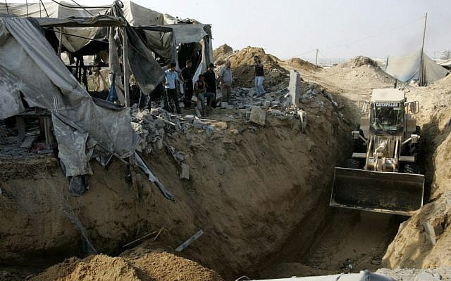 A Caterpillar bulldozer clears the area where a smuggling border tunnel between the Gaza Strip and Egypt was targeted by an Israeli air strike at dawn in Rafah, southern Gaza, on July 14, 2011. (photo credit: Abed Rahim Khatib/Flash90)