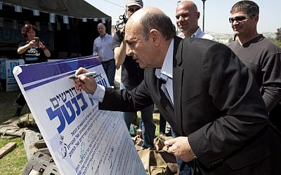 "Kadima chairman Shaul Mofaz symbolically signs a petition for universal conscription at the ""Suckers' Tent"" in Jerusalem on April 22, 2012. (photo credit: Flash90)"