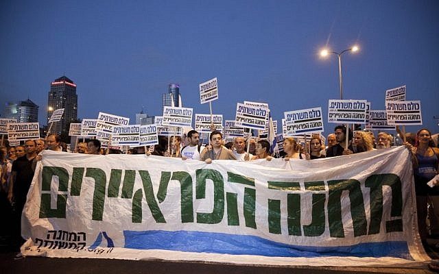 "Thousands rally in Tel Aviv on Saturday night behnd a banner that reads ""Suckers' Camp"" (photo credit: Tali Mayer/Flash90)"
