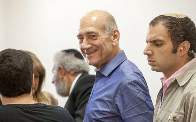 Former prime minister Ehud Olmert grins in the courtroom during his corruption trial. (photo credit: Emil Salman/Flash90)
