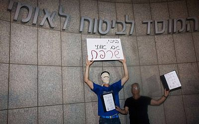 Protesters hold a sign reading 'Bibi you burned me, too' in front of the National Insurance Institute in Tel Aviv in mid-July (photo credit: Tali Mayr/Flash90)