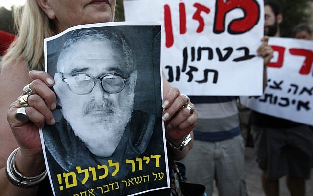 Social justice protesters chant slogans as they hold up pictures of Moshe Silman, who set himself on fire during a social justice demonstration in Tel Aviv (photo credit: Miriam Alster/Flash90)