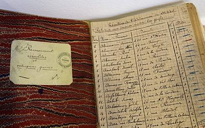 Documents coming from the Archives of Paris Police Prefecture showing lists of Jewish people registered during WWII are presented for an exhibition of French archives on Shoah in Paris. Photos, signatures and records of personal possessions from many of the victims are on display at a Paris district town hall. (photo credit: AP Photo/Remy de la Mauviniere)