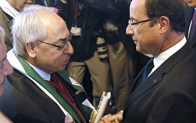 French President Francois Hollande (right) shakes hands with the leader of the Syrian National Council Abdulbaset Sieda during the Friends of Syria conference in Paris last month (photo credit: Patrick Kovarik/AP)