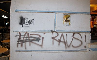Graffiti on the wall of the Moment cafe in Krakow's Kazimierz Jewish quarter read 'Nazi Raus!' and also cross out the 'anti' in 'anti-Fascist.'  (photo credit: Ruth Ellen Gruber/JTA)