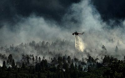A helicopter drops water on the US Air Force Academy as firefighters battle the blaze in Colorado Springs, Colorado, on June 27, 2012. (photo credit: US Department of Agriculture)