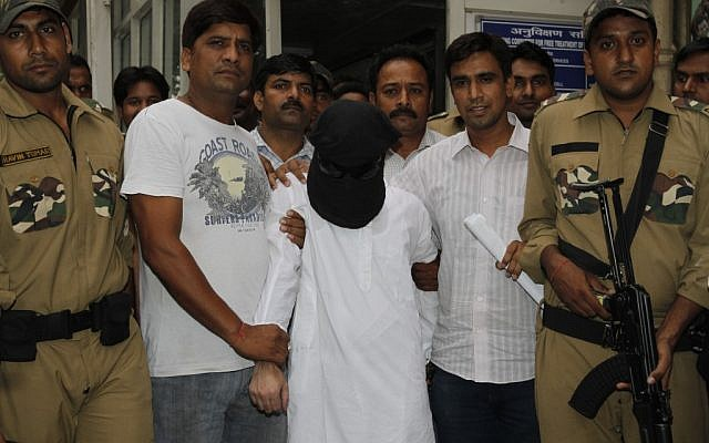 Delhi police officers escort Syed Zabiuddin Ansari, face covered, out of a government hospital after a medical checkup in India. (photo credit: AP)