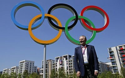 IOC President Jacques Rogge poses in front of the Olympic rings during his visit to the Athletes' Village at the Olympic Park in London, Monday, July 23, 2012. (photo credit: Jae C. Hong/AP)