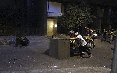 Protesters take cover behind makeshift barricades and throw rocks at Egyptian riot police during clashes outside the Syrian Embassy in Cairo, on July 18, 2012. (photo credit: Ahmed Gomaa/AP)