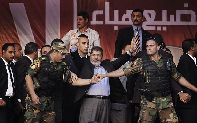 Egypt's new President Mohammed Morsi waves to supporters after giving a speech at Tahrir Square in Cairo on Friday, June 29. Morsi opened his jacket to show he was not wearing a bullet-proof vest. (photo credit: Khalil Hamra/AP)