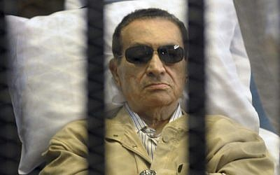 Egypt's ex-President Hosni Mubarak lays on a gurney inside a barred cage in the police academy courthouse in Cairo, Egypt, June 2012 (photo credit: AP)